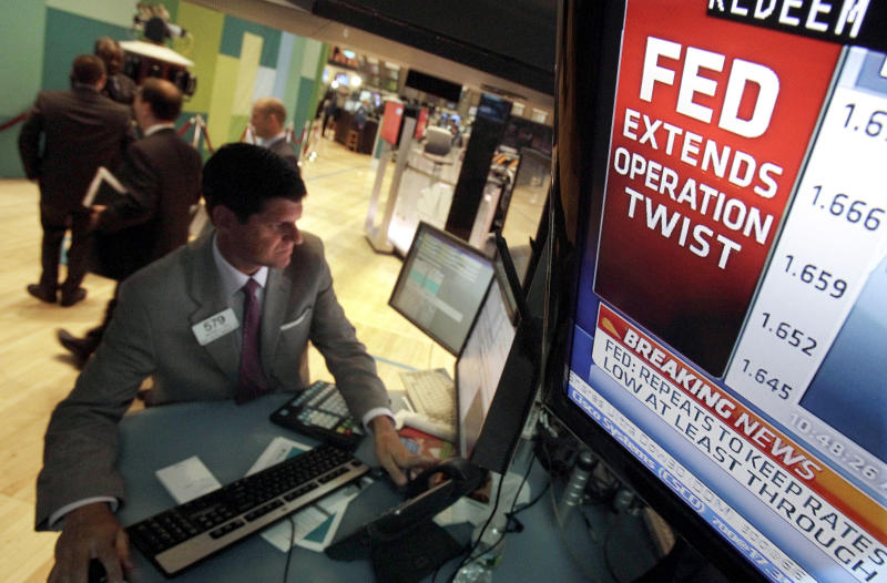 The decision of the Federal Reserve is visible on a television monitor at the trading post of specialist Michael Guli, on the floor of the New York Stock Exchange Wednesday, June 20, 2012. The Federal Reserve is extending a program designed to drive down long-term interest rates to spur borrowing and spending. (AP Photo/Richard Drew)