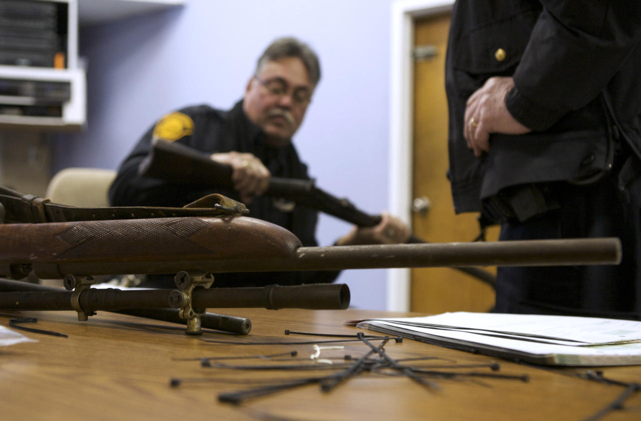 Bridgeport police officer Peter Garcia looks for a serial number on a rifle during a gun buyback event at the Bridgeport Police Department's Community Services Division in Bridgeport, Connecticut, in the wake of the shootings at Sandy Hook Elementary School, December 22, 2012. REUTERS/ Michelle McLoughlin (UNITED STATES - Tags: SOCIETY)