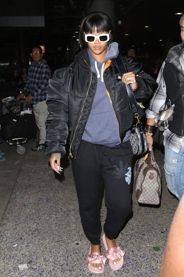 """<p>Leaving L.A. after her pop-up shop appearance, she upgrades herblack sweats,blue hoodie, and bomber withher own Fenty x Puma satin slidesand her favorite <a rel=""""nofollow"""" href=""""http://raen.com/shop/sunglasses/flatscreen/"""">Raen sunglasses</a><span></span>.</p>"""