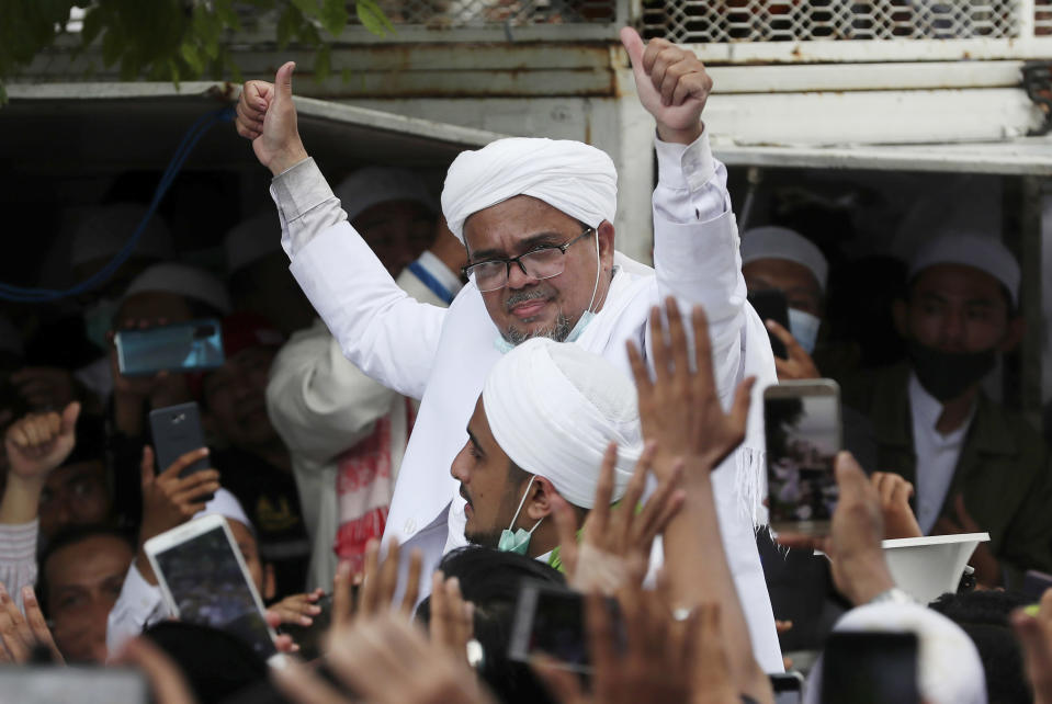 FILE - In this Tuesday, Nov. 10, 2020, file photo, Indonesian Islamic cleric and the leader of Islamic Defenders Front Rizieq Shihab, center, gestures to his followers as he arrives from Saudi Arabia in Jakarta, Indonesia. Shihab was sentenced to another four years in prison on Thursday, June 24, 2021, for concealing information about his coronavirus test result. (AP Photo/Achmad Ibrahim, File)