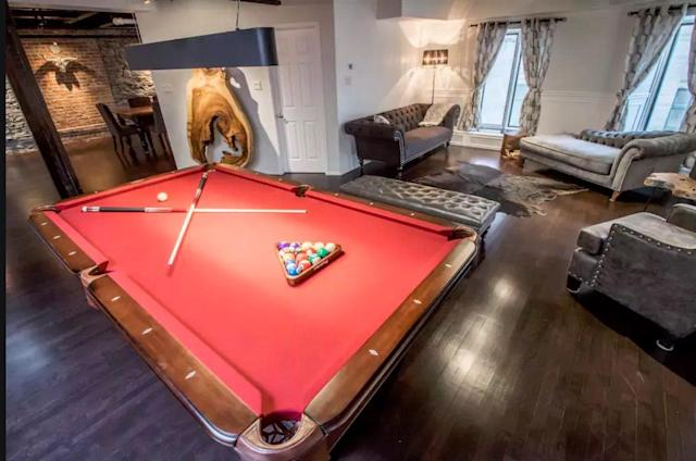 <p>The penthouse loft comes with a pool table, as well as its own foosball table. (Airbnb) </p>