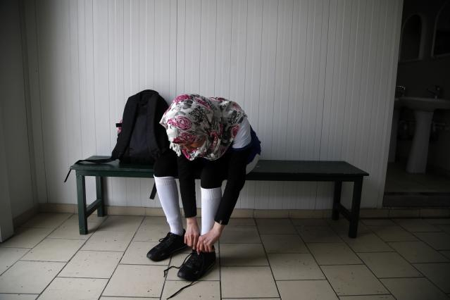 In this Wednesday, April 24, 2019 photo, Hiba from Iraq prepares for a training session of Hestia FC Women's Refugee Soccer team in Athens. Many of the players at Hestia FC weren't allowed to play or even watch soccer matches in their home countries. Hestia FC was set up by the Olympic Truce Centre, a non-government organization created in 2000 by the International Olympic Committee and Greek Foreign Ministry. (AP Photo/Thanassis Stavrakis)