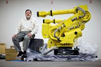 In this Jan. 15, 2013, photo, Rosser Pryor, Co-owner and President of Factory Automation Systems, sits next to a new high-performance industrial robot at the company's Atlanta facility. Pryor, who cut 40 of 100 workers since the recession, says while the company is making more money now and could hire ten people, it is holding back in favor of investing in automation and software. (AP Photo/David Goldman)