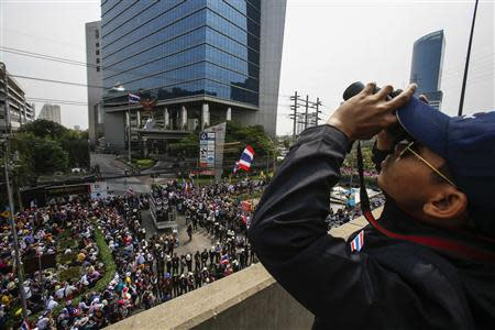 Anti-government protesters gather outside a business building owned by SC Asset Corp as a guard uses a pair of binoculars to scan high buildings around the protest site, during a rally in Bangkok February 20, 2014. REUTERS/Athit Perawongmetha