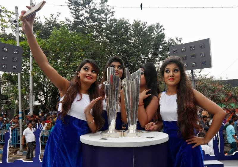 Models take a selfie next to the World Twenty20 trophies after they arrived in Kolkata