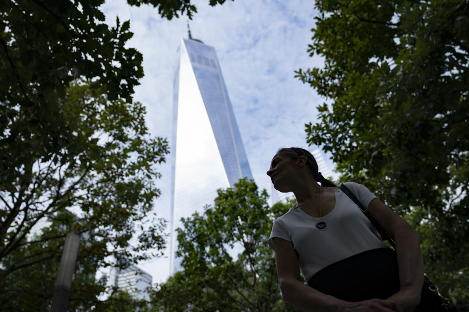 """Joan Mastropaolo, a 9/11 Tribute Museum board member, volunteer, and local Battery Park city denizen since 1998, stands amongst the trees at the 9/11 Memorial & Museum as One World Trade Center looms overhead, Monday, Aug. 16, 2021, in New York. Mastropaolo considered the area her front lawn after moving into the area for work in the late nineties, a natural transition from the previous decade when she worked in and around the World Trade Center. She shopped, attended concerts, and commuted through the site routinely. """"This vibrant community became nothing in a matter of a hundred and two minutes on the morning of Sept. 11,"""" said Mastropaolo. """"When they started bringing the trees to this site, for me, that was a symbol of returning life."""" (AP Photo/John Minchillo)"""