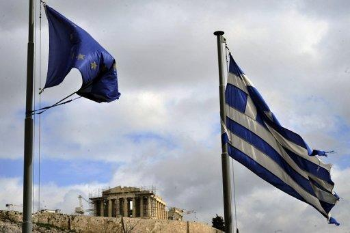 Ripped EU and Greek flags flutter in Athens. European Commission President Jose Manuel Barroso is due to meet Prime Minister Antonis Samaras as officials threw together a list of 11.6 billion euros in spending cuts to jumpstart reforms