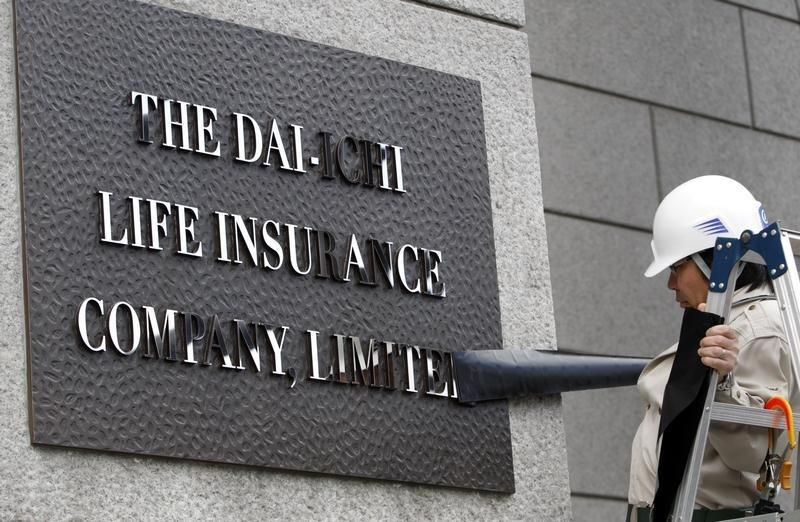 A worker removes masking tape from the new sign board of Dai-ichi Life Insurance Company, Limited at its headquarters in Tokyo