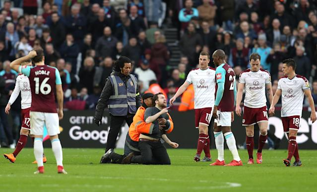 A West Ham fan is detained by a steward on the field. (Getty)