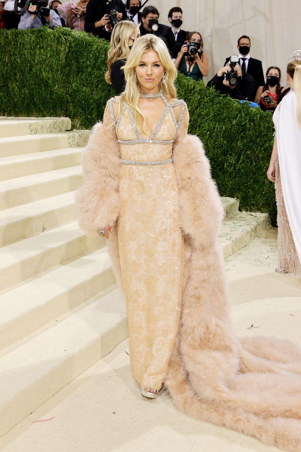 <p>Sienna Miller wore a nude Gucci dress and matching feather coat.</p>