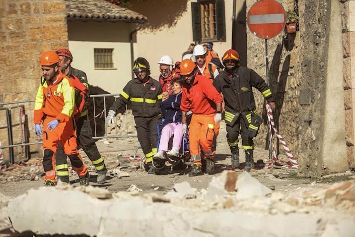 Firefighters on October 30, 2016 carry a woman from her home following massive earthquake in Norcia (AFP Photo/Fabrizio Troccoli)