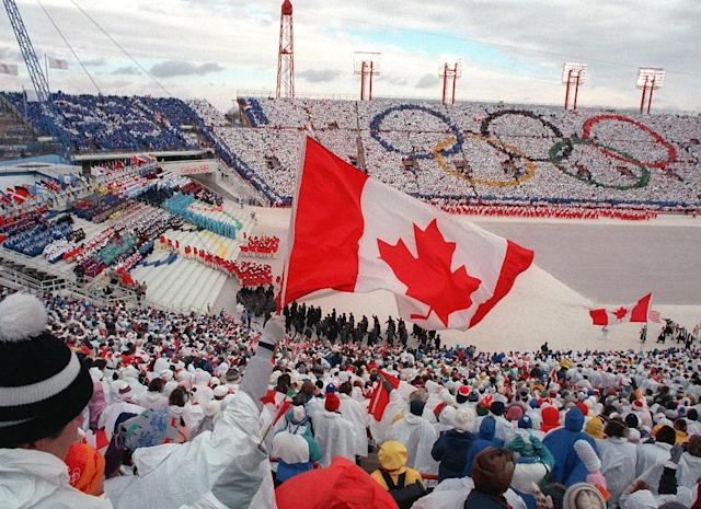Fans cheer and wave flags as the Canadian delegation (lower right) parades during the opening ceremony of the XVth Winter Olympic Games in Calgary in 1988 (AFP Photo/JONATHAN UTZ)