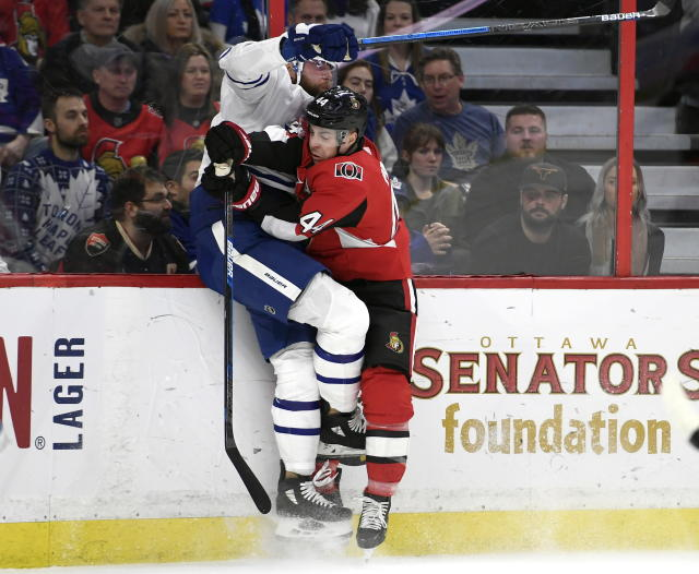 Ottawa Senators center Jean-Gabriel Pageau (44) crashes into the boards with Toronto Maple Leafs defenseman Jake Muzzin (8) during first-period NHL hockey game action in Ottawa, Ontario, Saturday, Feb. 15, 2020. (Justin Tang/The Canadian Press via AP)