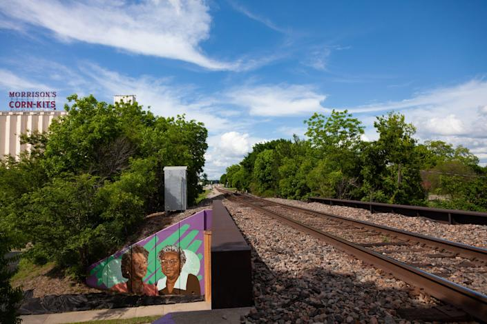 Train tracks, with a colorful mural to the side.