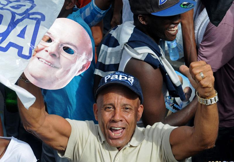 A supporter of former president and candidate for the opposition Dominican Revolutionary Party, Hipolito Mejia, holds a mask with Mejia's face during a closing campaign rally in Santo Domingo, Dominican Republic, Friday May 18, 2012. Dominicans will go the polls to elect a new president on Sunday. (AP Photo/Manuel Diaz)