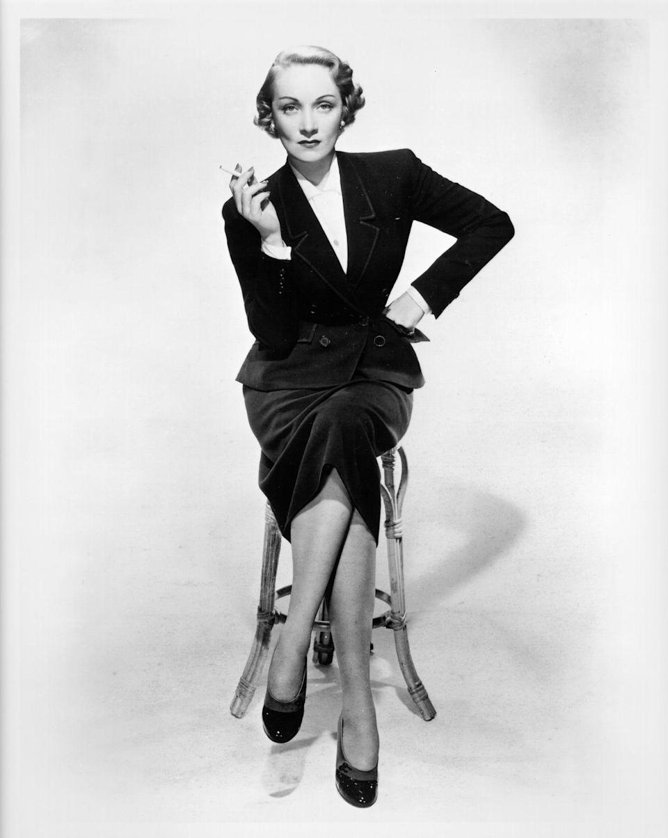 <p>Here, Dietrich poses for a studio portrait wearing her signature menswear. The formality of the black velvet suit set and heels are offset by her casual cigarette in hand. <br></p>