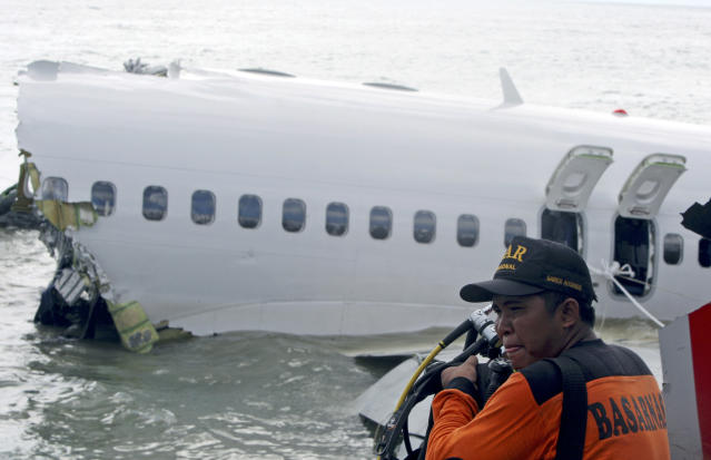A rescue worker prepare to retrieve a Lion Air jet plane's cockpit voice recorder out of the wreckage of the plane near the Ngurah Rai International airport in Kuta, Bali, Indonesia on Monday, April 15, 2013. The Indonesian passenger jet carrying 108 people missed the runway as it came into land on the resort island on Saturday, slamming into the water at high speed and splitting in two. (AP Photo/Firdia Lisnawati)