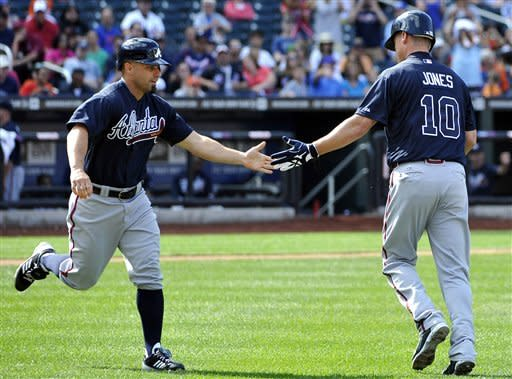 Atlanta Braves' Reed Johnson shakes hands with Chipper Jones (10) as Johnson jogs in to pinch run for Jones in the ninth inning of a baseball game against the New York Mets,Sunday, Sept. 9, 2012, at Citi Field in New York. (AP Photo/Kathy Kmonicek)