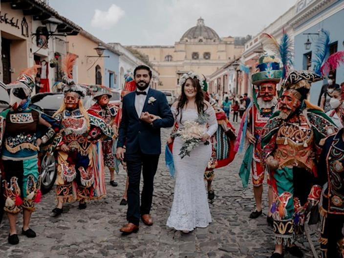 A bride and groom walk between a group of men dressed in traditional Guatemalan garb.