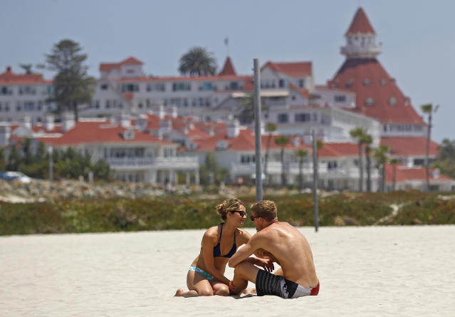 """FILE - In this May 22, 2012, file photo, a couple sits on the sand on Coronado Beach in Coronado, Calif. Stephen Leatherman, a coastal scientist and professor at Florida International University, has been drafting a list of the best beaches in the U.S. under alias """"Dr. Beach"""" since 1991. This year he has named Coronado Beach the ninth-best in the country. (AP Photo/Lenny Ignelzi, File)"""