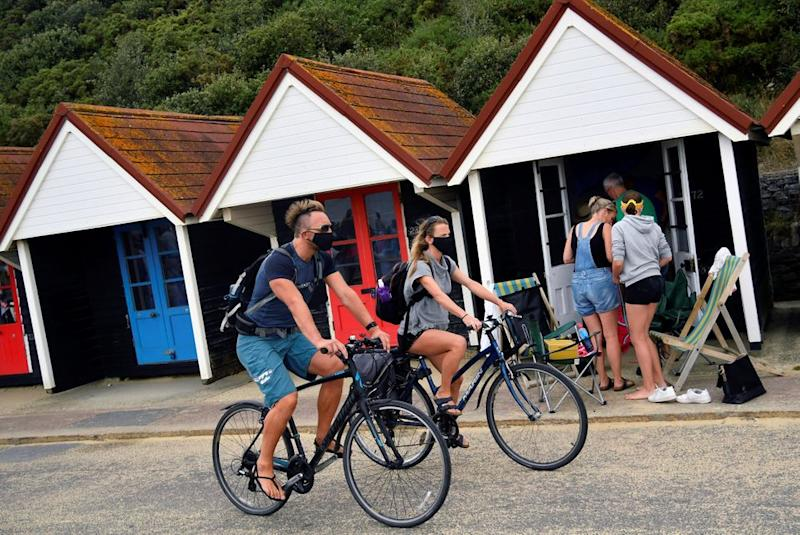 People wear protective face masks as they cycle along the seafront past the beach huts in Bournemouth.