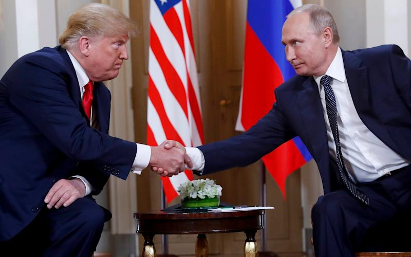 Donald Trump and Vladimir Putin, pictured in July last year - AP