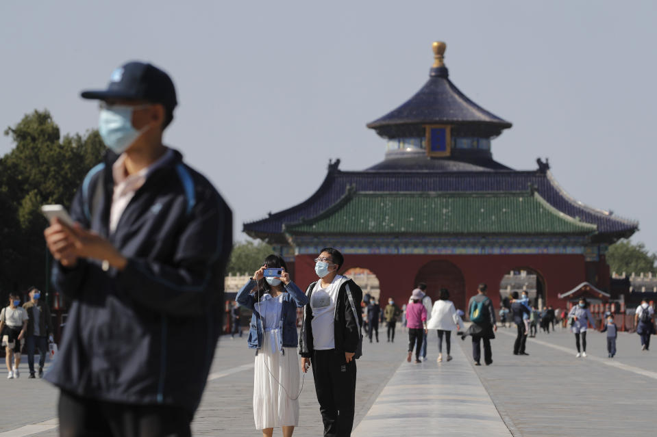 Visitors wearing protective face masks to help curb the spread of the new coronavirus visits the capital's popular tourist spot of Temple of Heaven in Beijing, Sunday, May 10, 2020. A family in China, nightclubs in South Korea and a slaughterhouse in Germany: New clusters of coronavirus infections are igniting concerns about a second wave even as calls grow in some countries to relax restrictions even further. (AP Photo/Andy Wong)