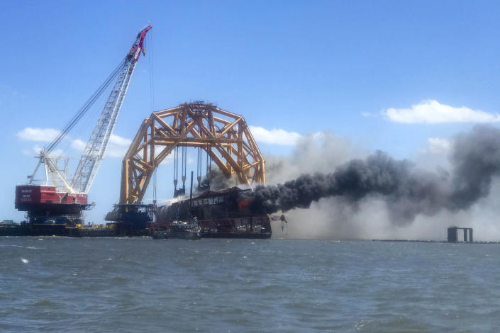 In this photo provided by the Altamaha Riverkeeper, smoke pours from the remnants of the capsized cargo ship Golden Ray on Friday, May 14, 2021, off St. Simons Island, Ga. Crews have spent months dismantling the ship in gigantic chunks after it overturned in September 2019. (Susan Inman/Altamaha Riverkeeper via AP)
