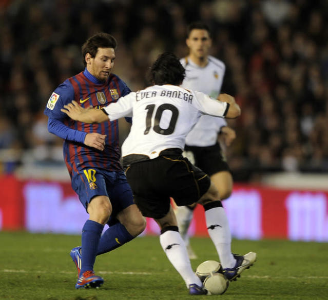 Barcelona's Argentinian forward Lionel Messi (L) vies for the ball with Valencia's Argentinian midfielder Ever Banega (R) during the Spanish Cup semi-final match Valencia CF vs Barcelona on February 01,2012 at the Mestalla stadium in Valencia. (Photo by Jose Jordan /AFP/Getty Images)