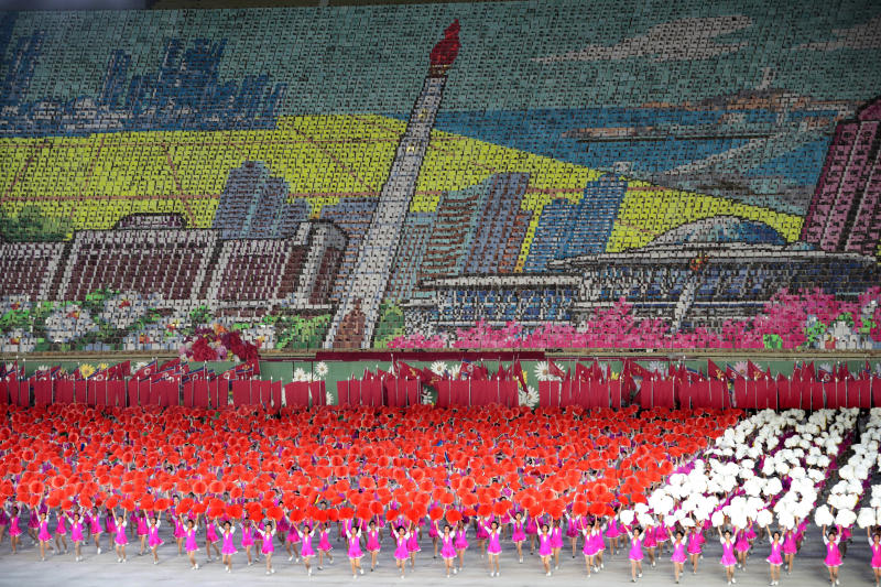 """In this Sept. 11, 2019, photo, North Korean dancers perform as mosaic of The Tower of The Juche Idea is formed during a mass games performance titled: """"The Land of the People"""" at May Day Stadium in Pyongyang, North Korea. It's just a single word, but it's hard to miss in North Korea: Splashed across countless propaganda signs, seeded through dozens of state media reports, at the beating heart of emotional pop songs and on the lips of the earnest guides who show off the grand monuments built in its honor. The word is Juche, and while it's technically a political ideology, in its difficulty for many outsiders to grasp, its ability to inspire devotion among North Koreans, and its ubiquity as a symbol of state power, it can seem more like a religion. (AP Photo/Dita Alangkara)"""