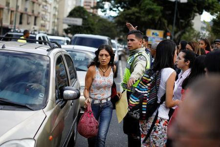 A police officer tries to control the traffic while people walk on the street during a blackout in Caracas, Venezuela February 6, 2018. REUTERS/Carlos Garcia Rawlins