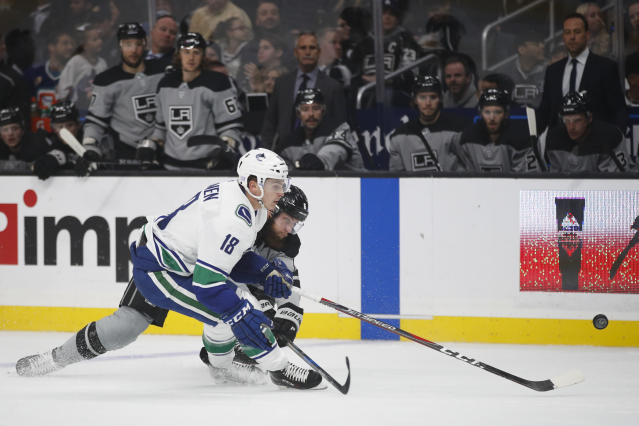 Vancouver Canucks' Jake Virtanen, front, and Los Angeles Kings' Jake Muzzin chase the puck during the first period of an NHL hockey game Saturday, Nov. 24, 2018, in Los Angeles. (AP Photo/Jae C. Hong)