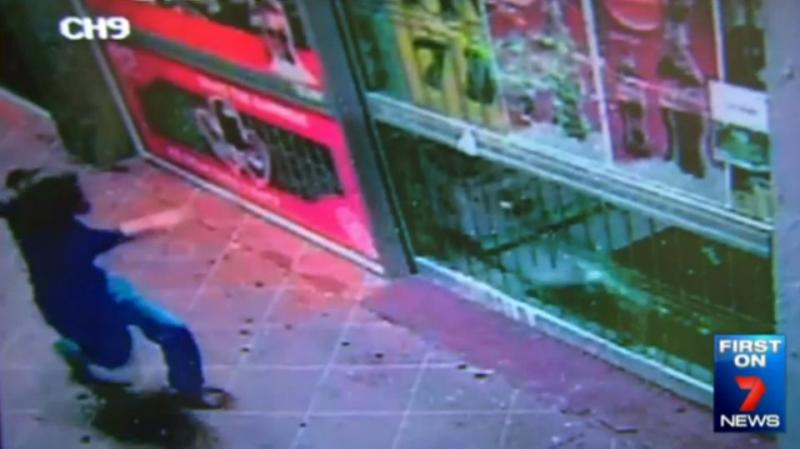 CCTV caught the moment the woman throws a brick into a supermarket window at Riverview. Photo: 7 News