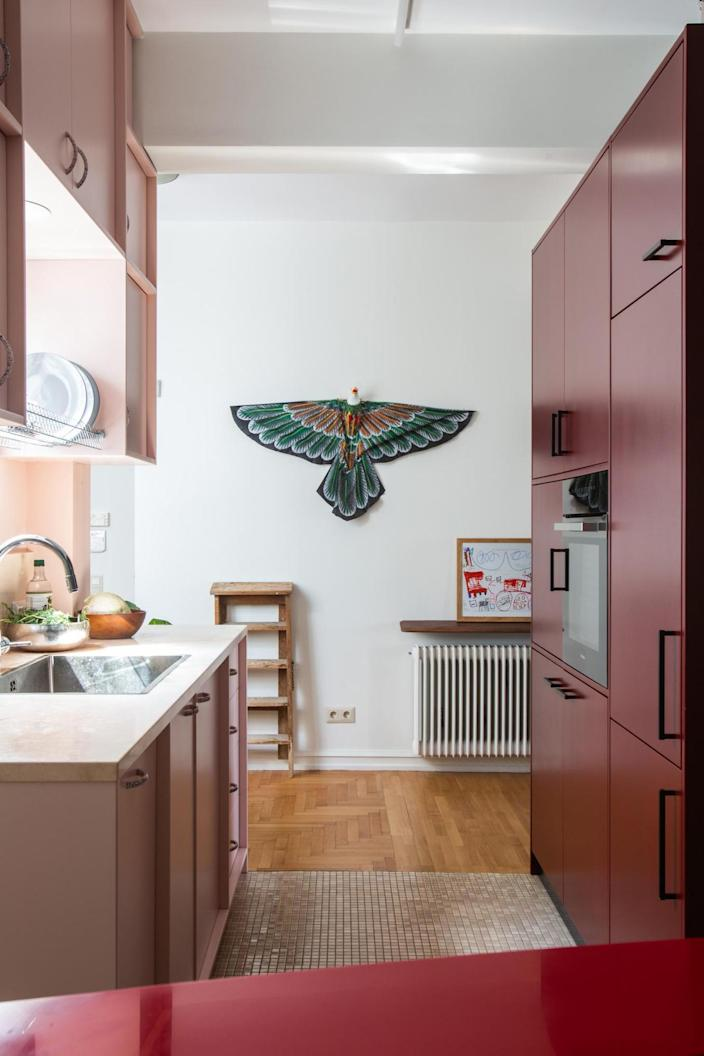 Colorful pink kitchen area inside Point Supreme's renovated Athens apartment.