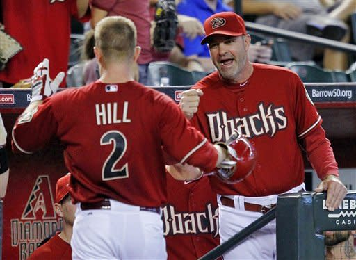 Arizona Diamondbacks' Aaron Hill (2) is greeted in the dugout by manager Kirk Gibson after hitting a home run during the first inning of an interleague baseball game against the Seattle Mariners, Wednesday, June 20, 2012, in Phoenix. (AP Photo/Matt York)