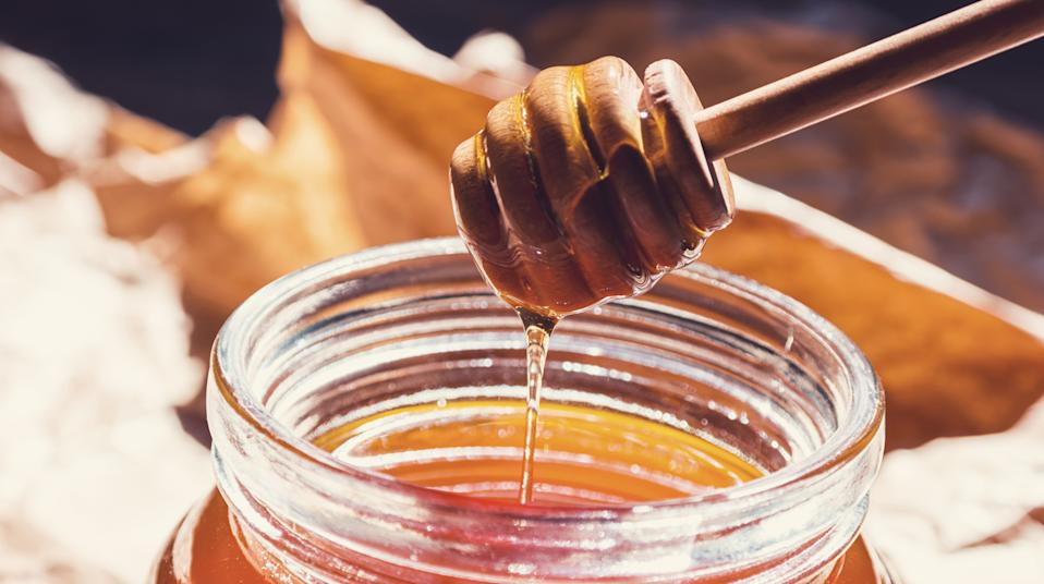 Closeup of a wooden honey dipper that dips in honey in a honey pot. ideal for websites and magazines layouts