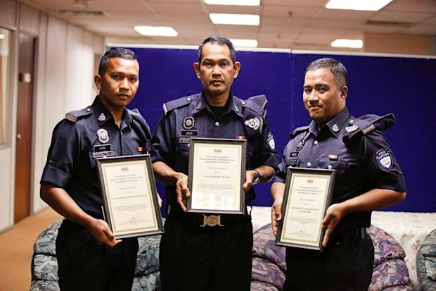 Zaidi Salleh (centre), Mohd Fitri Abu Hassan (left) and Megat Taufik Megat Kamarudin are presented with appreciation certificates by the National Safety Council April 20, 2018. ― P   icture by Sayuti Zainudin
