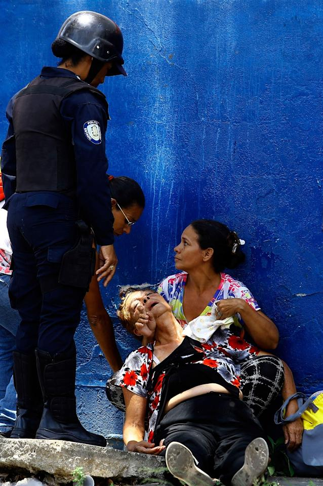 <p>A woman is overcome by tear gas that was used to disperse the relatives of prisoners who were waiting to hear news about their family members imprisoned at a police station where a riot broke out, in Valencia, Venezuela, Wednesday, March 28, 2018. In a state police station housing more than one hundred prisoners, a riot culminated in a fire, requiring authorities to open a hole in a wall to rescue the inmates. (Photo: Juan Carlos Hernandez/AP) </p>