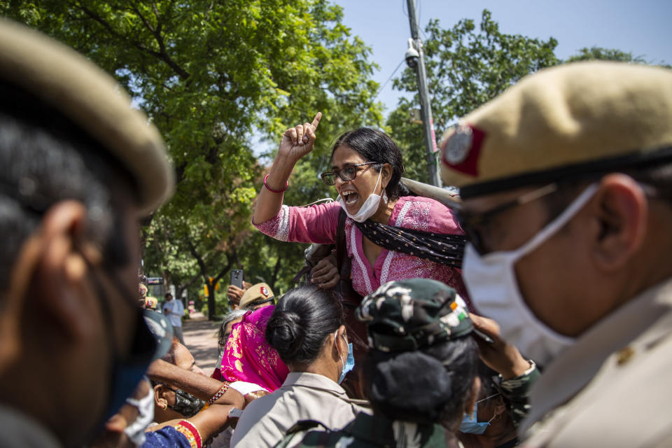 An Indian activist shouts slogans as she is detained by police during a protest in New Delhi, India, Wednesday, Sept. 30, 2020. The gang rape and killing of the woman from the lowest rung of India's caste system has sparked outrage across the country with several politicians and activists demanding justice and protesters rallying on the streets. (AP Photo/Altaf Qadri)