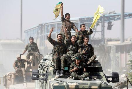 FILE PHOTO: Kurdish-led militiamen ride atop military vehicles as they celebrate victory over Islamic State in Raqqa