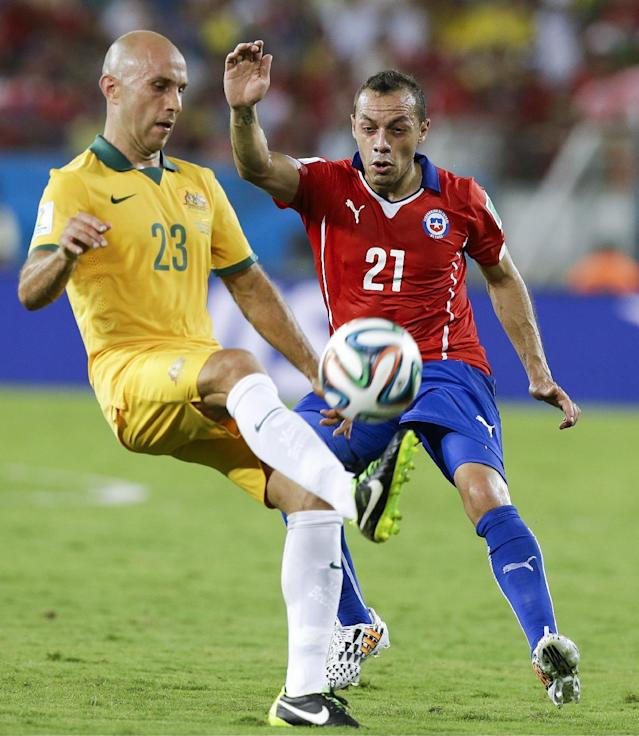 Australia's Mark Bresciano (23) tries to get the ball past Chile's Marcelo Diaz (21) during the first half of the group B World Cup soccer match between Chile and Australia in the Arena Pantanal in Cuiaba, Brazil, Friday, June 13, 2014. (AP Photo/Thanassis Stavrakis)