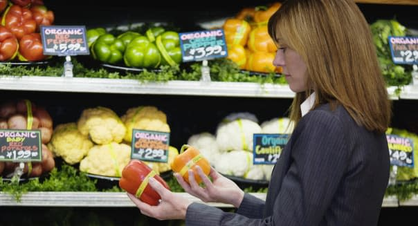 Woman comparing peppers in grocery store