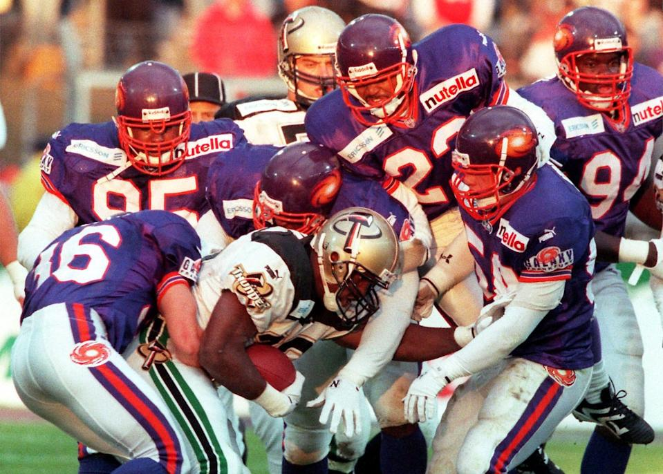 George Harris of the Berlin Thunder is tackled by Jim Cantelupe (36), Vince Amey (95), Michael Reed (23), Whit Marshall (front right) and Kendrick Gholston (94) during an NFL Europe match against the Frankfurt Galaxy at Frankfurt's Waldstadium in 1999.
