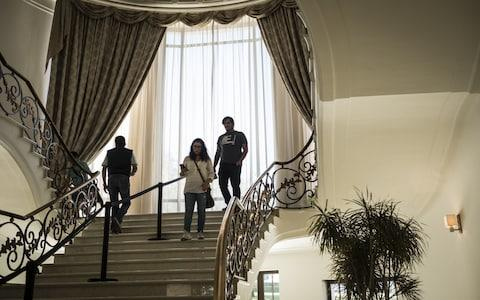 Visitors walk down a foyer in the Miguel Aleman house at Los Pinos, the former official residence of the President of Mexico, in Mexico City - Credit: Bloomberg