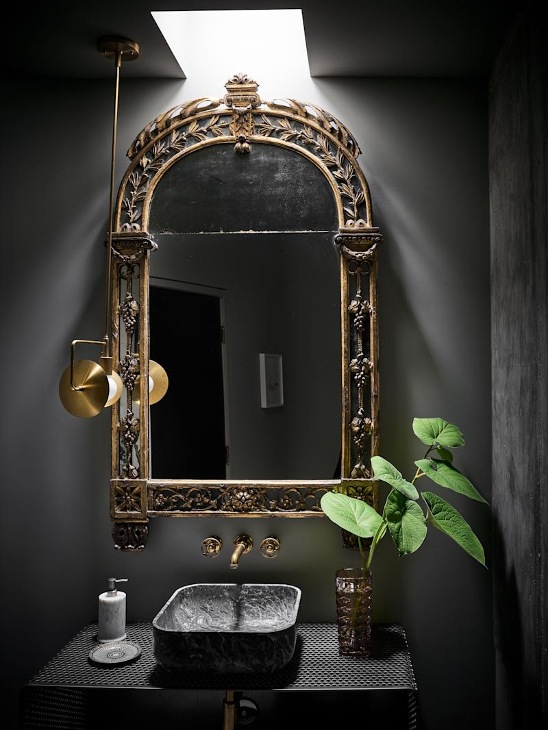 A moody powder room features a custom vanity made of perforated stainless steel and an Italian marble sink by Kreoo. The pendant is by Workstead, and the faucet is by Waterworks.