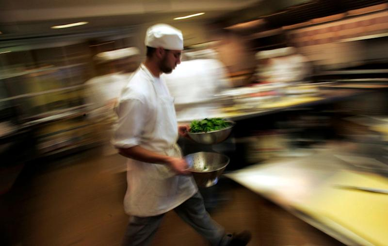 A culinary student rushes through the kitchen with greens during a class for aspiring professional chefs at The Institute of Culinary Education in New York City.