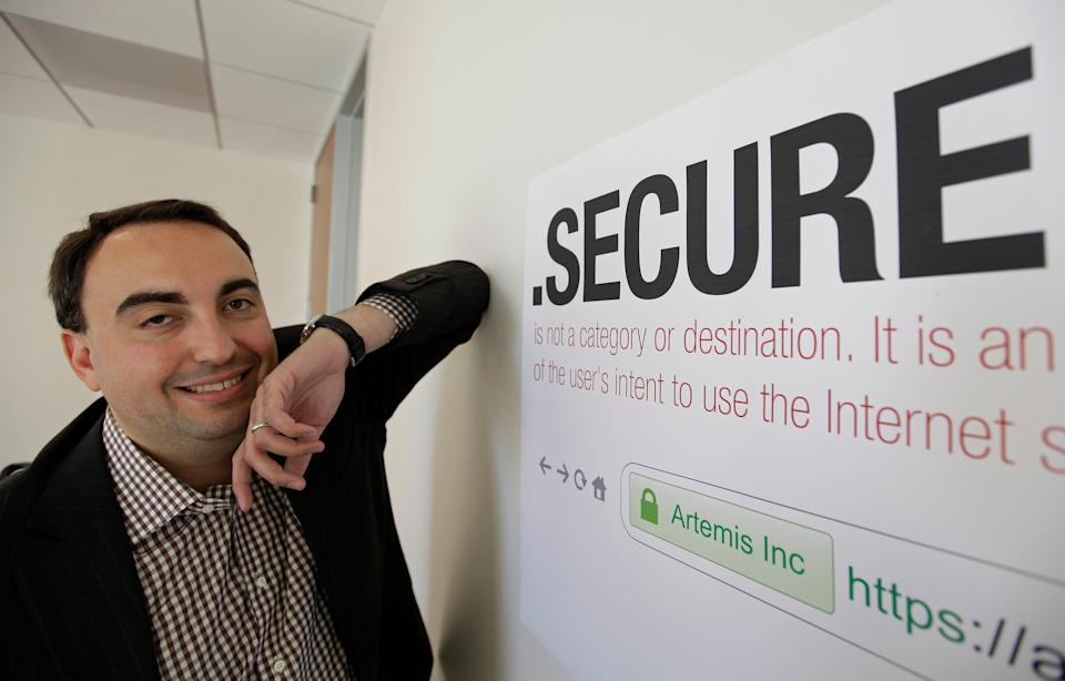 """FILE - In this photo taken Friday, June 8, 2012 Alex Stamos CTO of Artemis Internet, an NCC Group Company, poses by a domain name poster at their offices in San Francisco. Some 2,000 proposals have been submitted as part of the largest expansion of the Internet address system since its creation in the 1980s. These suffixes would rival """".com"""" and about 250 others now in use. The organization behind it, the Internet Corporation for Assigned Names and Numbers, will announce a full list and other details in London on Wednesday, July 26, 2017. (AP Photo/Eric Risberg, File)"""