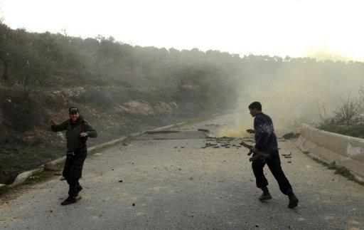 <p>The leader of a group of rebel fighters celebrates after detonating an IED used to cut road access to their stronghold in the northern Syrian province of Idlib on March 20. The UN Security Council demanded Wednesday that Syria immediately implement a peace plan by special envoy Kofi Annan, even as government forces pounded rebel zones around Damascus and Homs.</p>