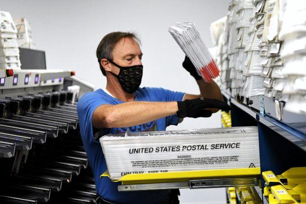 PHOTO: Michael Duve places mail-in ballots into trays in the sorting room at the Orange County Supervisor of Elections office in Orlando, Fla., Oct. 26, 2020. (Nurphoto/NurPhoto via Getty Images)