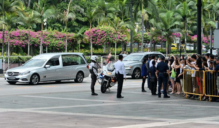 A crowd watches as a hearse carrying Lee Kuan Yew's remainds arrives at Istana presidential palace
